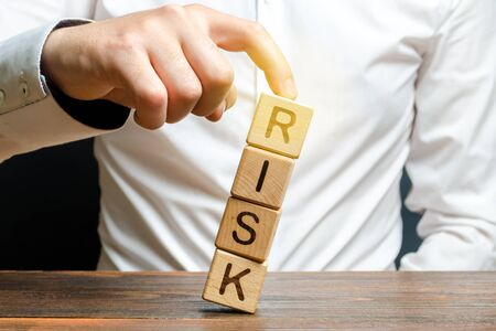 Businessman rescues with his finger a tower of cubes with the word Risk from falling Risk management, cost assessment, business and investment safety. Strengthen business resilience and flexibility.