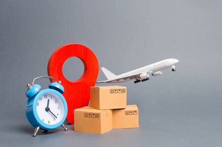 Airplane and stack of cardboard boxes, red position pin and blue alarm clock. concept of air cargo and parcels, airmail. Fast delivery of goods and products. Cargo aircraft. Logistics, connection