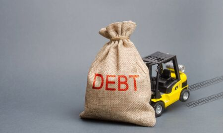 Yellow forklift truck can not lift the bag with the inscription debt. Inability to repay a loan, debt restructuring. High business load, lack of support, high competition. Unprofitable enterprise.