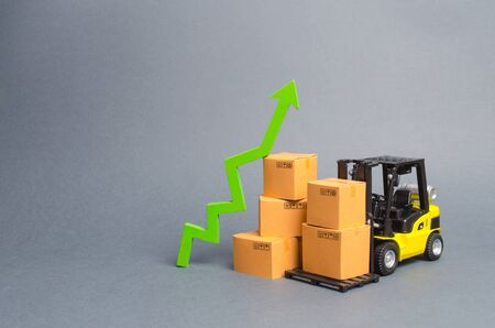 Yellow Forklift truck with cardboard boxes and a green arrow up. growth rate of production goods and products, raise economic indicators. Increasing consumer demand. exports and imports. sales rise