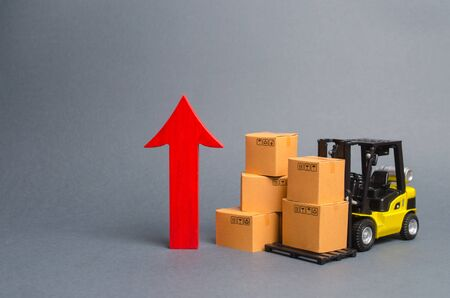 Yellow Forklift truck with cardboard boxes and a big red arrow up. increase in trade between countries, popularity of national goods, economic growth. growth rate of production goods and products, Archivio Fotografico