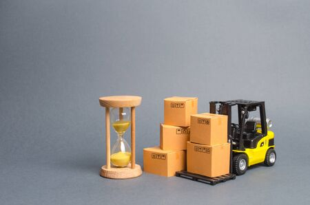 Yellow Forklift truck with cardboard boxes and a sand hourglass. Express delivery concept. Optimization of logistics and delivery, improving efficiency. Temporary storage, limited offer and discount.