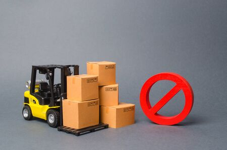 Forklift truck near cardboard boxes and a red symbol NO. Embargo, trade wars. Restriction on the importation of goods, proprietary for business. Inability to sell products, ban import. No delivery.