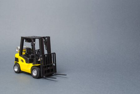 Yellow forklift truck on gray background. Warehouse equipment, vehicle. Logistics and transport infrastructure, industry and agriculture. Unloading, transportation, sorting, loading cargo.