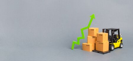 Forklift truck with cardboard boxes and a green arrow up. growth rate of production goods and products, economic raise . Increasing consumer demand. exports and imports. sales rise. Banner, copy space