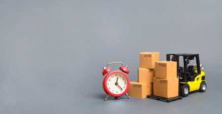 Yellow Forklift truck with cardboard boxes and a red alarm clock. Express delivery concept. Temporary storage, limited offer and discount. Optimization of delivery logistics. Banner, copy space