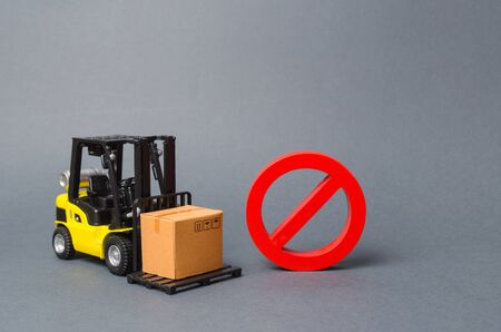 Forklift truck carries a cardboard box near a red symbol NO. Embargo, trade wars. No delivery. Restriction on the importation of goods, proprietary for business. Inability to sell products, ban import