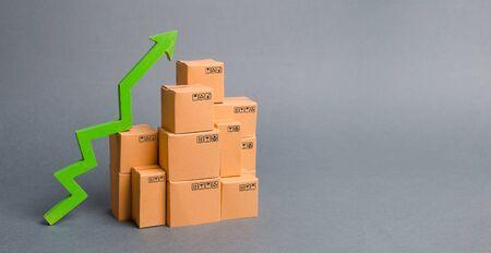 Molte scatole di cartone e una freccia verde in alto. tasso di crescita dei beni di produzione, aumentare gli indicatori economici. Aumento della domanda dei consumatori. esportazioni e importazioni. aumento delle vendite. Alta produttività, logistica.
