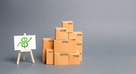 Lots of cardboard boxes and stand with green up arrow. Growth of income from the sale of goods. Price increase. The growth rate of production. Increasing consumer demand. exports and imports rise Archivio Fotografico