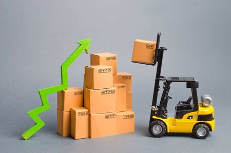 Yellow Forklift truck raises a box over a stack of boxes and a green arrow up. High trade volumes, increased production, storage infrastructure. raise economic indicators. exports, imports. sales rise Archivio Fotografico