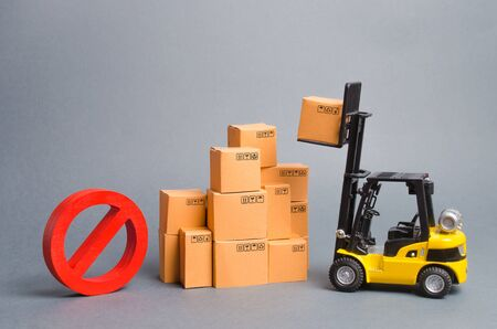 Yellow Forklift truck truckraises a box over a stack of boxes and a red symbol NO. Embargo trade wars. Restriction on importation of goods, ban on export of dual-use goods to countries under sanctions Imagens