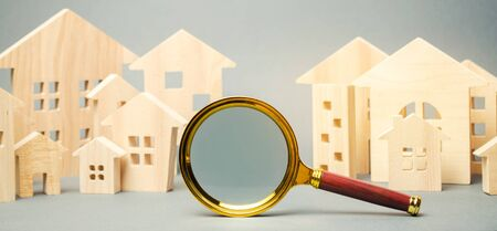 Magnifying glass and wooden houses. House searching concept. Home appraisal. Property valuation. Choice of location for the construction. Search for housing, apartments. Real estate appraiser services Foto de archivo