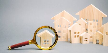 Magnifying glass and wooden houses. House searching concept. Home appraisal. Property valuation. Choice of location for the construction. Search for housing, apartments. Real estate appraiser services Banque d'images