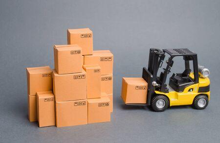 Il carrello elevatore giallo porta la scatola a una pila di scatole. Industria e produzione. magazzini e trasporti. aumentare gli indicatori economici. esportazioni, importazioni. aumento delle vendite. aumento della produzione Archivio Fotografico