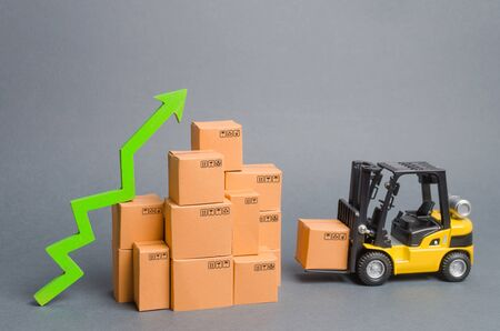 Yellow Forklift truck brings the box to a stack of boxes and a green arrow up. raise economic indicators. exports, imports. sales rise. High trade volumes, increased production, storage infrastructure