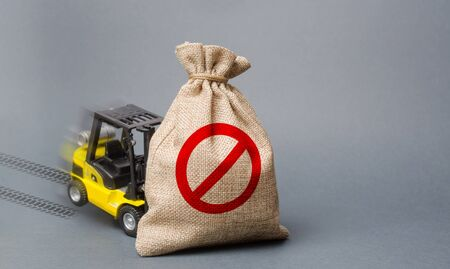Yellow forklift truck can not lift the bag with the symbol NO. Economic pressure and sanctions. trade wars, stagnation. Restriction on the importation of goods, proprietary for business.