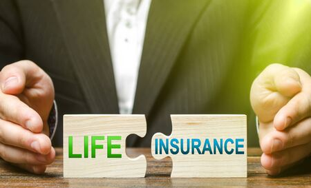 Businessman lays out puzzles with inscriptions life insurance. Medical service providing affordable medicine at the expense of enterprises or the state. Health maintenance and monitoring, prevention.