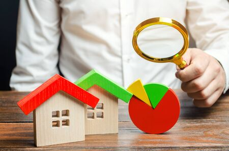Businessman holding a magnifying glass over a pie chart and a wooden houses. Concept analysis of the real estate market. Mortgage arrears. Investing in construction. Buying and selling housing. Debts