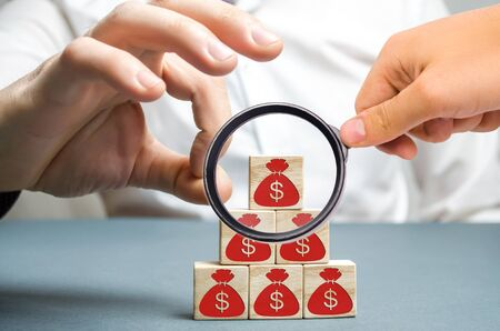 Businessman removes a cube with a picture of dollars. Bankruptcy concept. Economic recession. Financial crisis. Capital outflow. Sabotage of the economy. Pressure on small businesses. Falling prices.