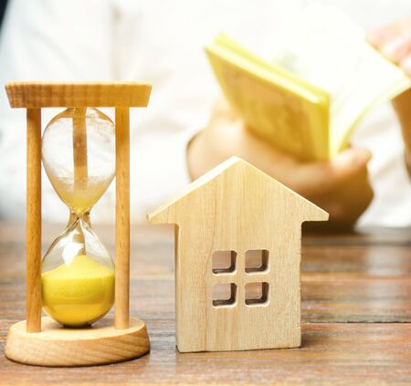 Wooden house and clock. Businessman counting money. Payment of deposit or advance payment for renting a home or apartment. Long-term mortgage on the house. Tax and mortgage vacations. Pledge 版權商用圖片