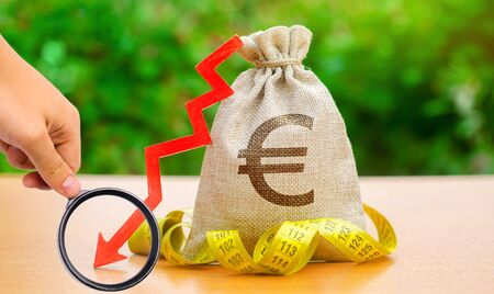 Bag with money and tape measure with arrow to down. Falling wages and welfare. Low profits and liquidity of investments. The concept of bankruptcy. Bad business payback. Capital outflow. Euro