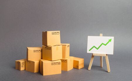 Plenty of cardboard boxes and whiteboard with green positive chart arrow up. Increasing consumer demand. rate growth of production of goods and products, increasing economic indicators. Foto de archivo