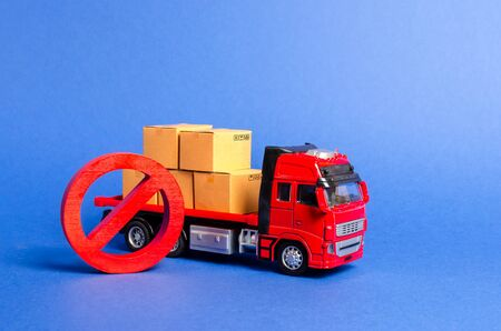 A red truck loaded with boxes and a red symbol NO. Embargo trade wars. Restriction on importation, ban on export of dual-use goods to countries under sanctions. transport companies. Ban on transit