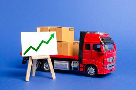 Red truck loaded with boxes and stand with a green up arrow. Raise economic indicators and sales. Exports, imports. High trade volumes, growth production, storage infrastructure Transit and delivery