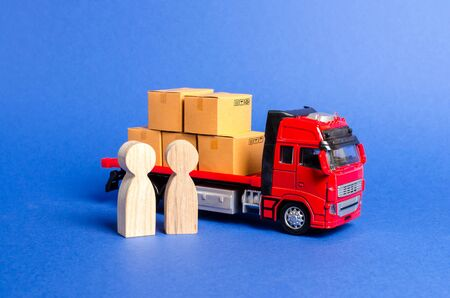 A red truck loaded with boxes near a customer buyer and seller. Business and commerce. Negotiations on supply of goods. Services transportation of goods and products, logistics Transportation company.