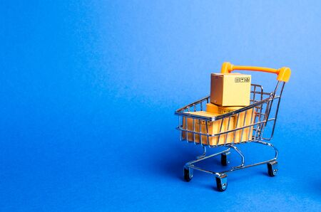 Supermarket cart with boxes, merchandise: the concept of buying and selling goods and services, internet commerce, online shopping, trade and turnover. Import and export, purchasing power.