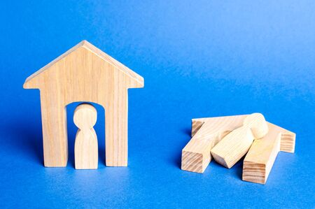Figures unscathed and broken homes with tenants. The concept of indifference and no help in natural distress and catastrophes. War conflict. Assistance to refugees and victims, humanitarian mission. Stock Photo