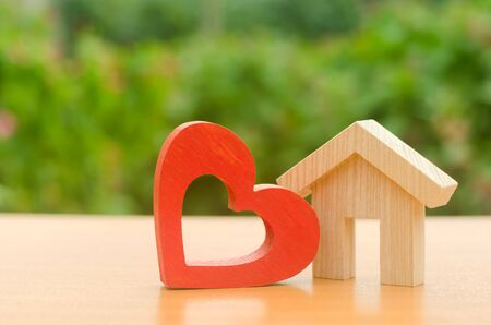House with a red wooden heart. House of lovers. Affordable housing for young families, support program. Parental hospitable home. Housing construction of your dreams. Buying and renting real estate.