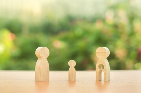 Child's figure stands between father and mother. The child chooses which parent to live with after their divorce. Guardianship over child. Taking into account the interest of child, payment of alimony Standard-Bild