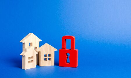 Three houses and a red padlock. Unavailable and expensive real estate. house Insurance. Security and safety. Confiscation for debts. alarm system. seizure of property. Protection of property rights. Stock Photo