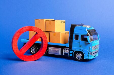 A blue truck loaded with boxes and a red symbol NO. Embargo trade wars. Restriction on importation, ban on export of dual-use goods to countries under sanctions. transport companies. Ban on transit Imagens