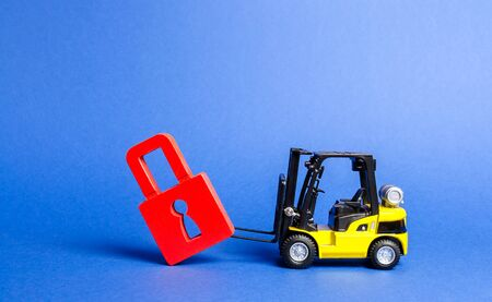 A yellow forklift tilts a red padlock from the road. Bypassing prohibitions and sanctions restrictions, lobbying the interests of industry in government. Loopholes in the laws, overcoming bans.