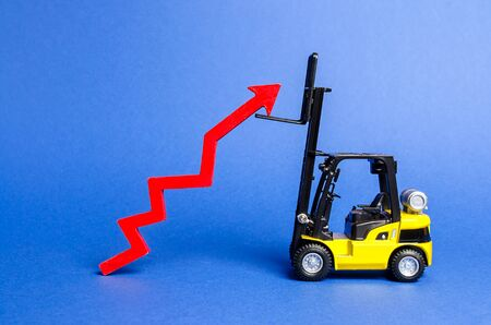 A yellow forklift raises a big red arrow up. Growth in production rates and development of industry and infrastructure. Increased sales, economy growth. Concept of increase, growth and success.