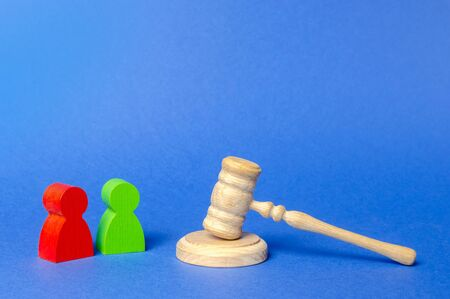Two figures of people opponents stand near the judges gavel. The judicial system. Court case, settling disputes. Legal advice, lawyer services. Conflict resolution in court, claimant and respondent.