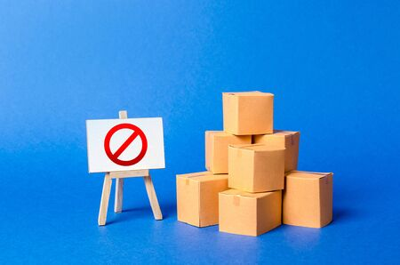 A stack pile cardboard boxes and a sign stand with red symbol NO. Restriction on the importation of goods, proprietary for business. Embargo, trade wars. Inability to sell products, ban on the import.