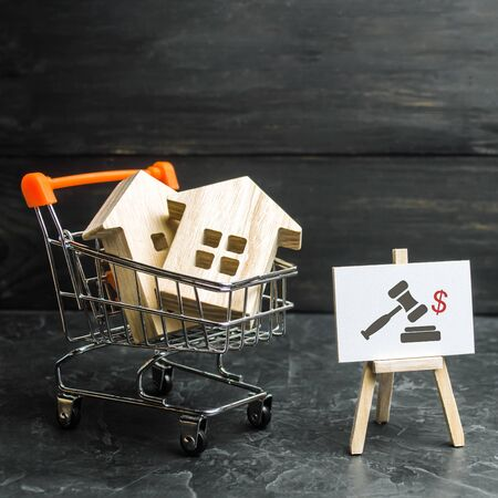 Wooden houses in a supermarket cart. uction for the purchase of housing and buildings. The growth of the city and its population. Investments. concept of rising prices for housing or rent