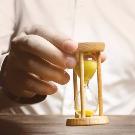 The person holds an hourglass in his hands. Business management. Logistics, process efficiency, savings. Time management. Awareness of time constraints. Pension, countdown, deadline. Self discipline Stock Photo