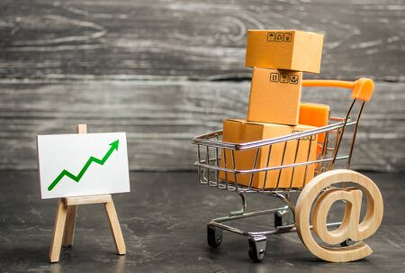 Shopping cart filled with boxes, email symbol and stand with green up arrow. shopping online. Growth rate of Internet sales, advertising services. E-commerce. sales of goods and services