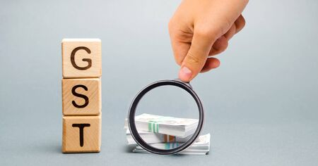 Wooden blocks with the word GST (Goods & Services Tax) and money. Tax, which is imposed on the sale of goods and services Reklamní fotografie