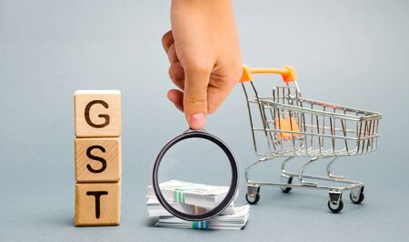 Wooden blocks with the word GST (Goods & Services Tax), money and a supermarket trolley. Tax, which is imposed on the sale of goods and services