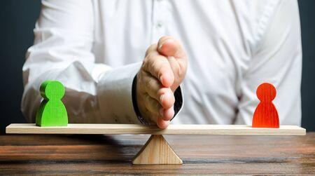 Ein Mann teilt mit seiner Handfläche zwei Personenfiguren von Gegnern auf der Waage. Zur Begründung und Beilegung des Konflikts zwischen den Parteien, der Lösung des Streits. Suchkompromiss, Vermittlerdienste.