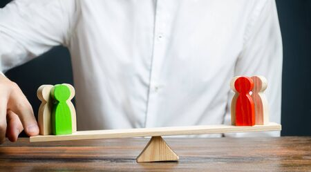 A man changes the balance of scales in favor of a green group of people. Mediator services. Conflict, dispute resolution, judicial system. Negotiations and decision making in favor of one of the sides