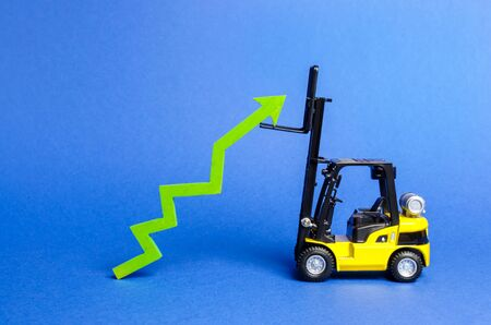 A yellow forklift raises a big green arrow up. Growth in production rates and development of industry and infrastructure. Increased sales, economy growth. Concept of increase, growth and success.