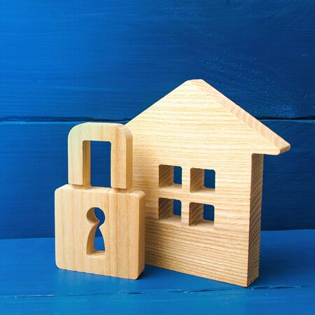 Wooden house with a padlock. Buying a home. House with a lock. Security and safety, collateral, loan for a mortgage. Confiscation of property for debts. Safety and alarm system. Stock Photo