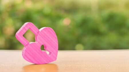 A pink padlock in shape of a heart. Heart health. The secret of relationships and the rules of a strong family. Strong love affair. Secrets, rumors and gossip. The concept of female intimate health.