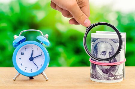 Alarm clock and money on green bokeh background. The concept of Time is money. Business financial ideas. Saving. Financial investments, revenue increase, budget management, savings account